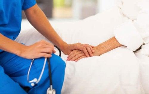 infermiere-che-tiene-la-mano-di-una-paziente