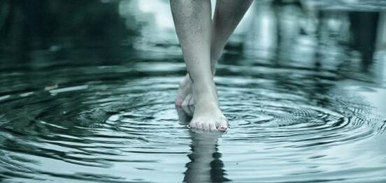 piedi che camminano in acqua