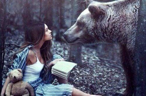 ragazza in mezzo ad un bosco di fronte ad un orso