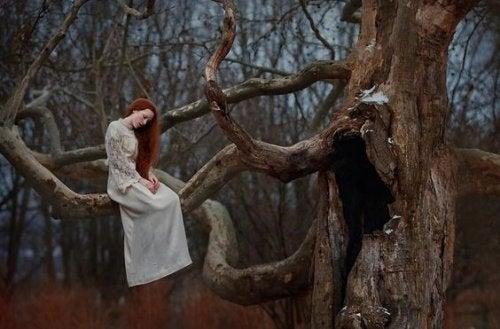 ragazza triste sul ramo di un albero