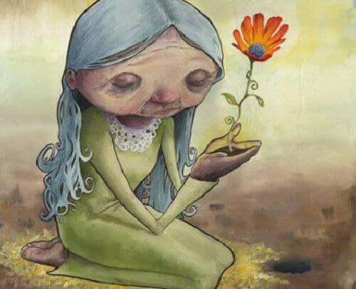 anziana in ginocchia con un fiore che nasce dalle sue mani