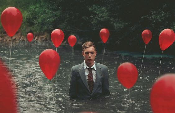 persona-immersa-nel-fiume-e-palloncini-rossi