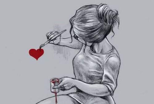 ragazza che dipinge un cuore sul muro