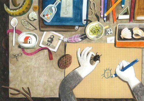 scrivania-con-molti-oggetti-e-persona-che-disegna
