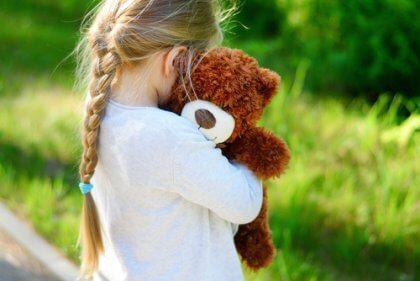 Bambina che abbraccia peluche.