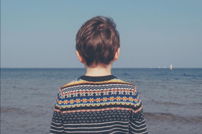 Bambino di spalle davanti al mare.