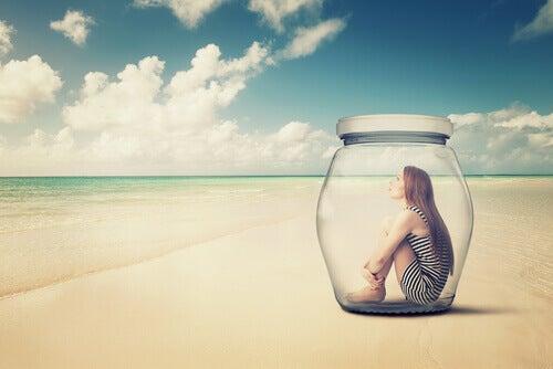 Donna chiusa in un barattolo di vetro sulla spiaggia