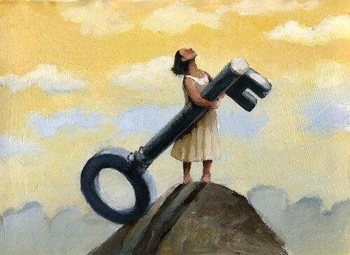 Donna che tiene una chiave sulla cima di una montagna