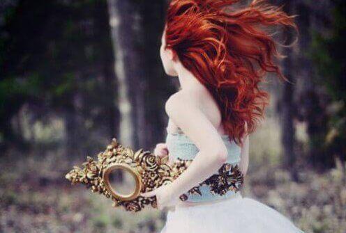 Donna con i capelli rossi corre tenendo uno specchio