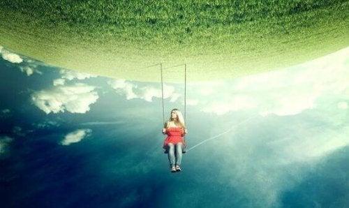 Donna su un'altalena in un mondo capovolto