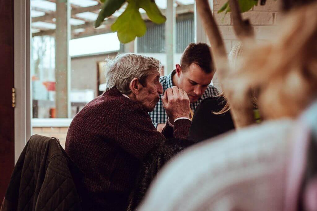Genitore anziano che fa colazione con il figlio accudire