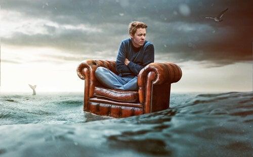 Uomo con fobia sociale su una poltrona in mezzo al mare
