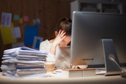 Donna davanti al computer con ansia per il molto lavoro