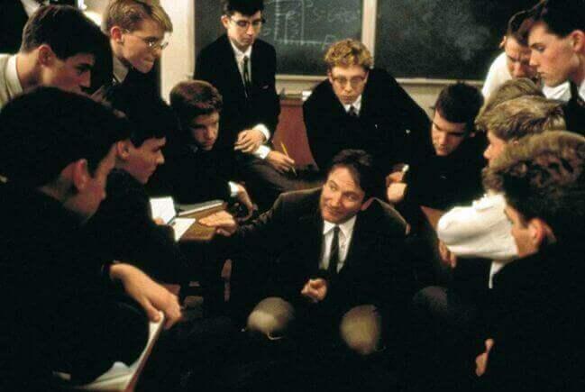 """Scena del film """"L'attimo fuggente"""" in cui il bravo insegnante è circondato dai suoi alunni"""