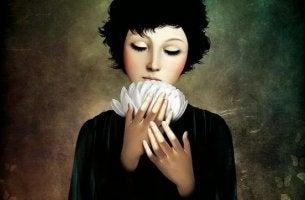 Ragazza con un fiore bianco tra le mani che conosce la gratitudine