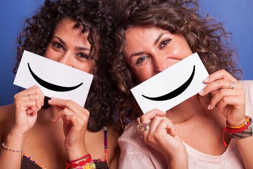 Amiche che tengono di fronte al volto un cartello con un sorriso