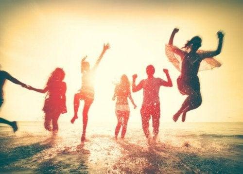 Amici che saltano felici in riva al mare