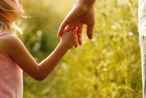 Bambina che afferra la mano di sua madre