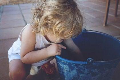 Bambina che cerca qualcosa nel secchio