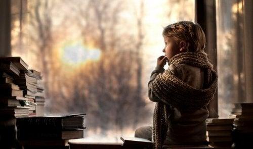 Bambina con sciarpa che guarda fuori dalla finestra