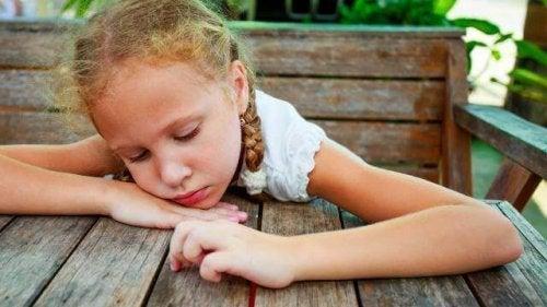 Bambina depressa appoggiata su di un tavolo