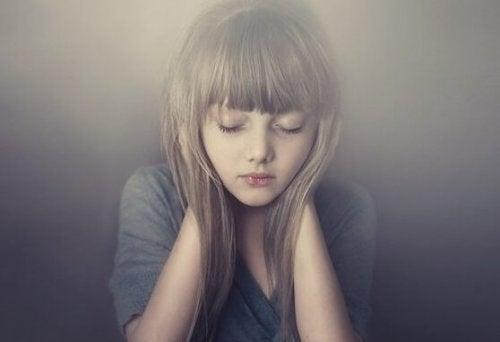 Bambina in silenzio con le mani sulle orecchie