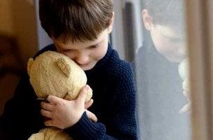 Bambino in una famiglia disfunzionale che abbraccia il suo orsacchiotto