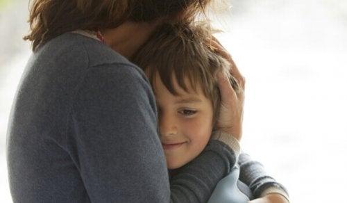 Bambino felice mentre viene abbracciato da sua madre
