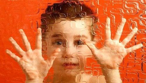 Bambino con le mani appoggiate su un vetro