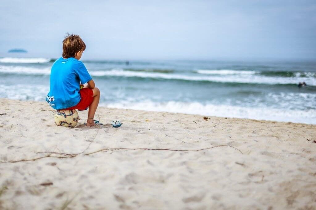 Bambino in spiaggia seduto su una palla mentre guarda verso il mare