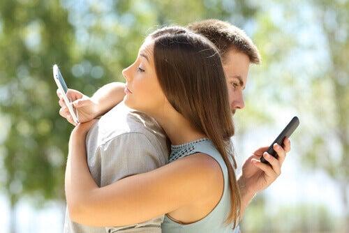 Coppia che si abbraccia e guarda il cellulare