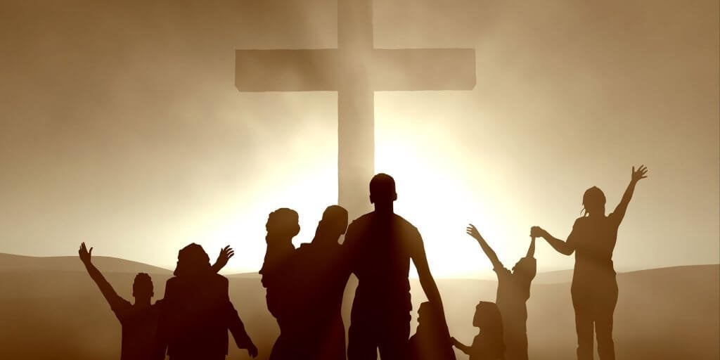 Gente felice davanti a una croce