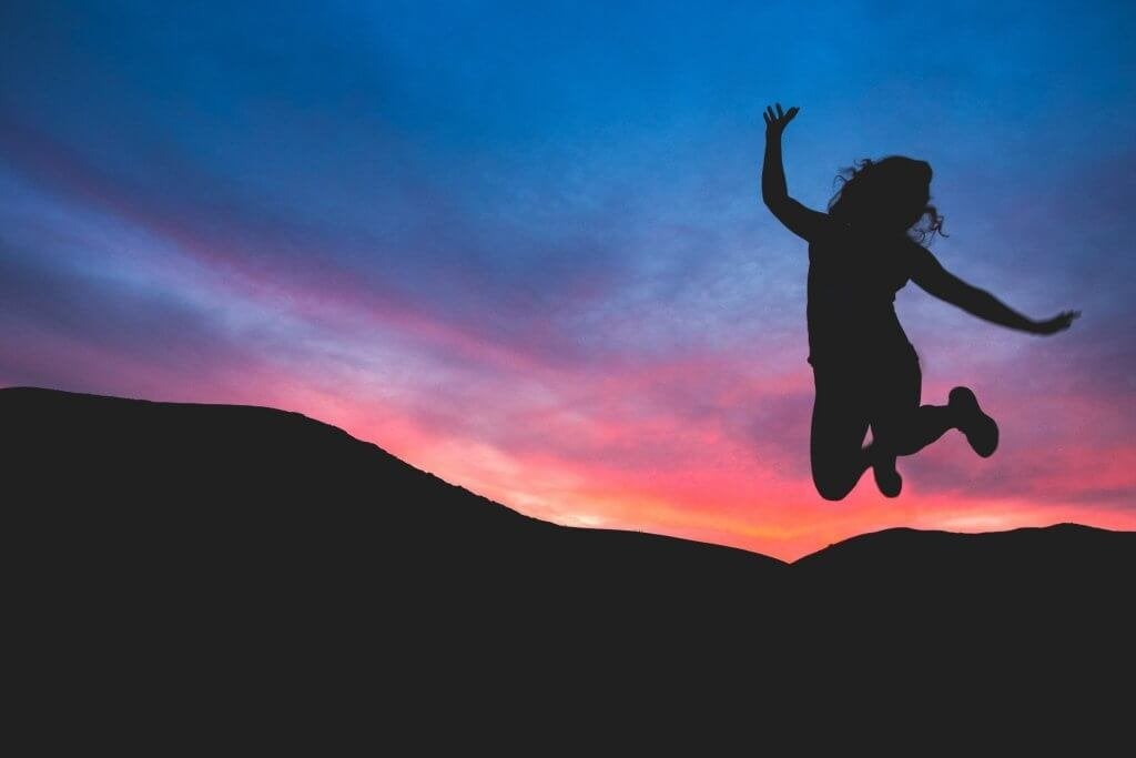 Donna che salta felice davanti ad un tramonto