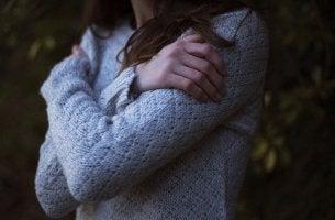Donna che abbraccia sé stessa