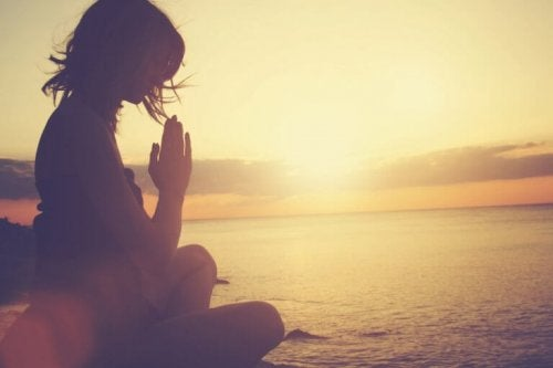 Donna seduta all'aperto mentre pratica la mindfulness