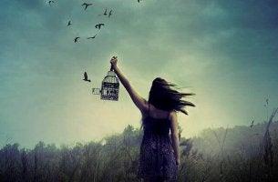 Donna che libera degli uccelli da una gabbia sentirsi soli