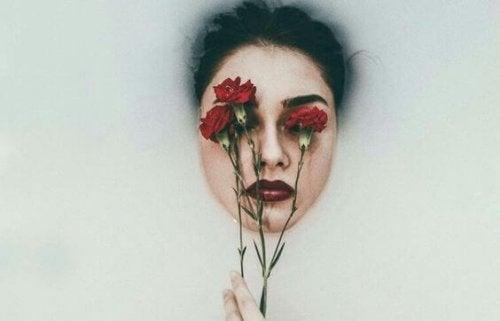 Viso di donna con fiori sugli occhi