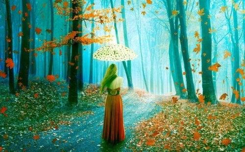 Donna con un ombrello mentre passeggia nel bosco