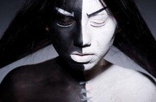 Donna con il volto dipinto per metà di nero e per metà di bianco, rappresentando luci e ombre