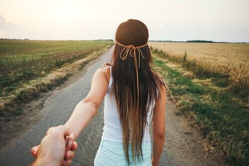 Ragazza di spalle che dà la mano al suo fidanzato