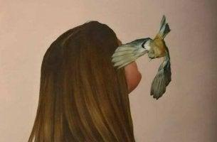 Donna con il volto coperto dall'ala di un uccellino