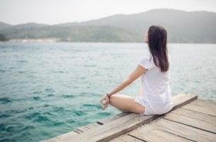 Ragazza che medita su un molo