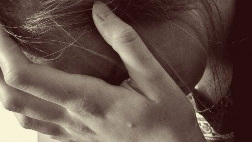 Donna affaticata con la mano sulla fronte