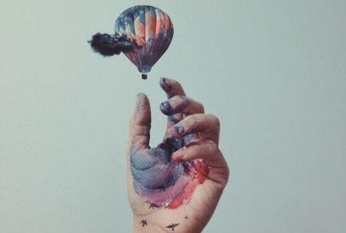 Mano con vernice che afferra una mongolfiera