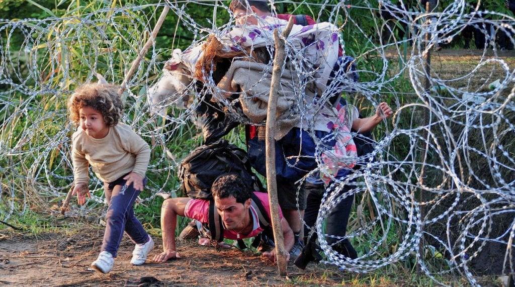 Famiglia di rifugiati che passa sotto il filo spinato