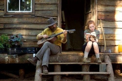 Captain fantastic ragazza che legge e uomo che suona la chitarra
