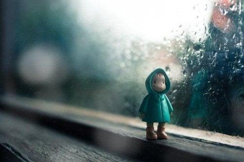 Pupazzetto di bambino davanti ad una finestra mentre fuori piove