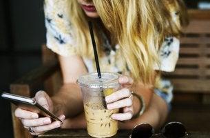 Ragazza con bevanda e cellulare che non sa connettersi con gli altri
