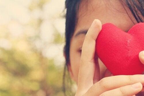 Ragazza che tiene di fronte al viso un cuore