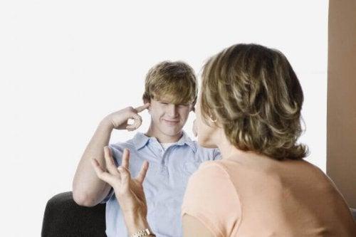 Ragazzo adolescente si tappa le orecchie per non sentire sua madre